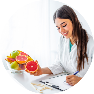 A young 'nutritionist' smiling while writing and holding a fresh grapefruit at her office at 'Sokratis Dragonas Chiropractor' Westfield NJ